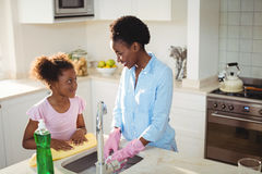 Mother assisting her daughter in cleaning utensils. At home Royalty Free Stock Photography