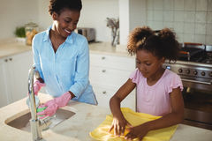 Mother assisting her daughter in cleaning utensils. At home Royalty Free Stock Image