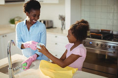 Mother assisting her daughter in cleaning utensils. At home Royalty Free Stock Photos