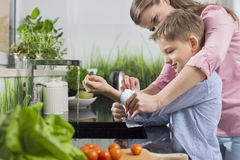 Mother assisting son in folding sleeves while washing hands in kitchen Stock Photos