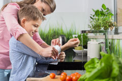Mother assisting son in folding sleeves while washing hands in kitchen Royalty Free Stock Photography
