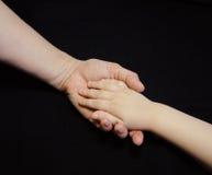 Mother att ge sig räcker till ett barn på svart bakgrund Royaltyfri Fotografi