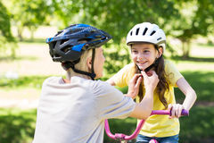 Mother attaching her daughters cycling helmet Royalty Free Stock Photos