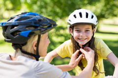 Mother attaching her daughters cycling helmet Royalty Free Stock Photography