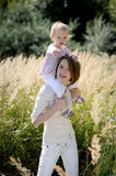 Mother with a baby. Mother giving piggyback ride to her baby pointing at you wih a finger Royalty Free Stock Image