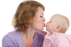 Mother with a baby. Gentle kiss. Mother kisses the daughter Royalty Free Stock Photography