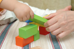 Mother and baby. A Chinese mother and her child are playing with wooden toy blocks Stock Photos