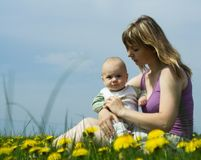 Mother and baby. A young mother and baby relax in a field of flowers