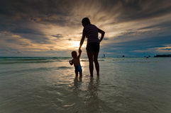 Mother and baby. Silhouette of a mother with her baby at sunset on a tropical beach stock images