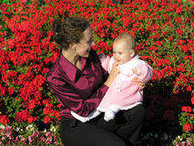 Mother with baby. On flowers stock photo