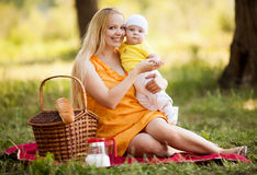 Mother and baby. Young mother and baby having a picnic outdoor on a warm summer day Stock Photography