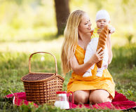 Mother and baby. Young mother and baby having a picnic outdoor on a warm summer day Royalty Free Stock Photo