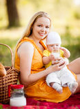 Mother and baby. Young mother and baby having a picnic outdoor on a warm summer day Stock Photos