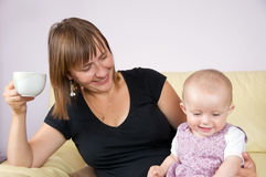Mother with baby. Happy mother drinking coffee and siting with baby on sofa royalty free stock images