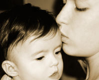 Mother and baby. Mother kissing her baby Royalty Free Stock Image