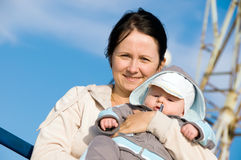 Mother and baby. Baby in mother's arms on blue sky background royalty free stock images