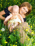 Mother and baby. Smiling mother and baby resting  in the park Stock Images