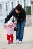 Mother and baby. Picture of a mother helping young daughter to walk Royalty Free Stock Photo