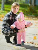 Mother with  baby against autumn Royalty Free Stock Image