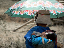 Mother and baby from Akha Hill Tribe. Sheltering from hot sun, Num Lin Mai village, Myanmar (Burma Stock Images