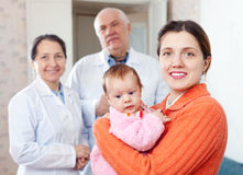 Mother with baby in arms against pediatrician Royalty Free Stock Photo