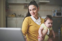 Mother with baby in arms sitting at home and working on laptop. stock images