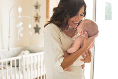 Mother with baby in arms. Young mother holding her baby in the bedroom Stock Photography