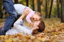 Mother and baby in Autumn. Side view of young mother playing with baby girl on Autumn leaves, trees in background royalty free stock photo