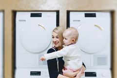 mother with baby on the background of washing machines stock photo