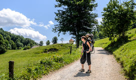 Mother with baby in backpack carrier is hiking in mountains. Royalty Free Stock Photo