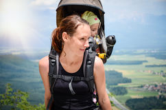 Mother with baby in backpack carrier is hiking in mountains. Tourist is carrying a child on his back in the nature of Slovenia with beautiful view of the Royalty Free Stock Photos