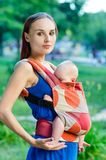 Mother and baby. In backpack. Outdoor Stock Image