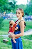 Mother and baby. In backpack. Outdoor Stock Photos