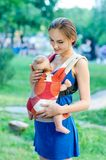 Mother and baby. In backpack. Outdoor Royalty Free Stock Photo