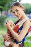Mother and baby. In backpack. Outdoor Stock Photo