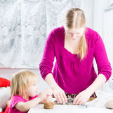 Mother with baby baking gingerbread cookies Royalty Free Stock Photos