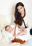Mother with baby in basket on bed, happy family portrait on white background Stock Photos