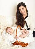 Mother with baby in basket on bed, happy family portrait on white background, yellow toned Royalty Free Stock Photo
