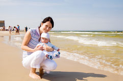 Mother with baby at the beach. Mother is embracing her baby at the beach royalty free stock photos