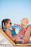 Mother with baby on beach playing with sunglasses Stock Image
