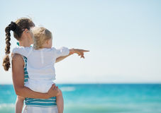 Mother and baby on beach pointing on copy space. Portrait of mother and baby on beach pointing on copy space stock photography