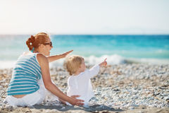 Mother and baby on beach pointing on copy space Stock Photos