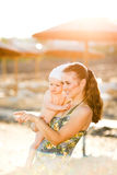 Mother with baby on beach showing something. Portrait of young mother with baby on beach showing something by pointing in corner Royalty Free Stock Images