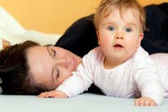 Mother and baby in bed. Funny portrait of blue eyed mother and baby daughter lying in bed next to each other Stock Image