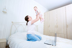 Mother and baby in bed.Child and parent together at home.Young m stock photo
