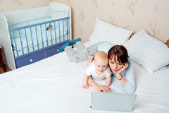 Mother with baby on the bed looking at a laptop with enthusiasm Stock Photo