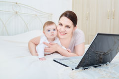 Mother and baby in bedroom smiling. Stock Photos