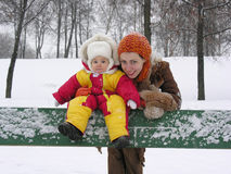 Mother with baby on bench. winter Royalty Free Stock Photo