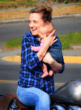 Mother Baby Bike Fun. A mother laughing with a newborn baby while sitting on a motorcycle. Shallow depth of field Royalty Free Stock Photography