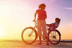 Mother and baby biking at sunset Royalty Free Stock Photography
